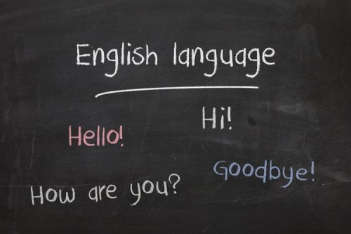 "A photo of a blackboard, with the words ""English Language; Hello! Hi! How are you? Goodbye!"" written on it in different colored chalk."