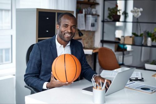 A sport business manager sits at an office desk while holding a basketball.