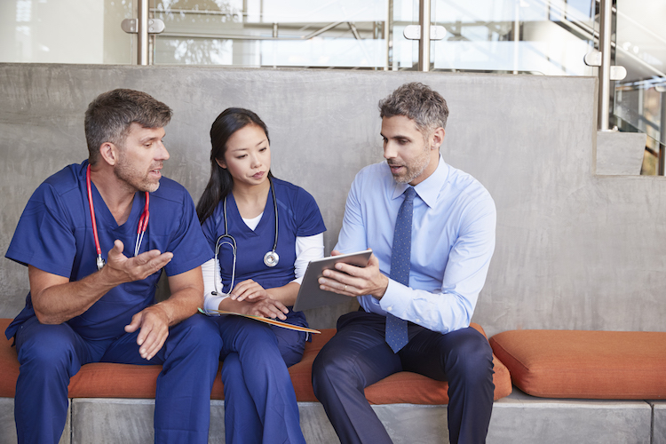 Registered nurses sit together in a hospital with an administrator