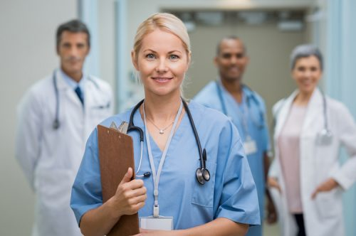 Group of nurses pose in their scrubs and white coats.