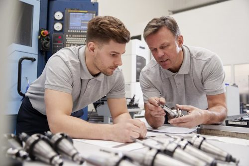 Engineer shows apprentice how to measure drawings.