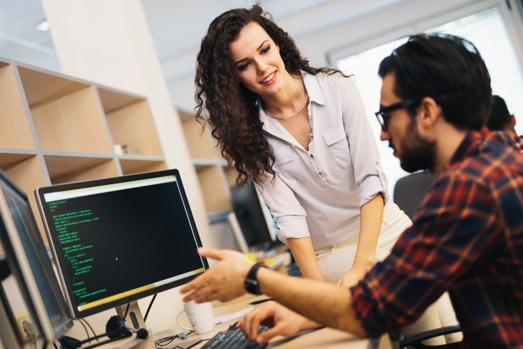 Data engineer analyzes computer data with a colleague