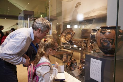 Docent educates child about artifacts.