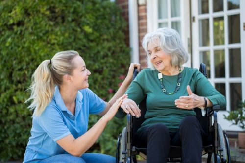 A nursing home caregiver assists a resident