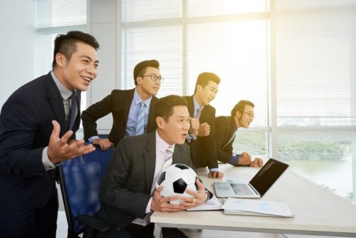Businessmen watch soccer match.