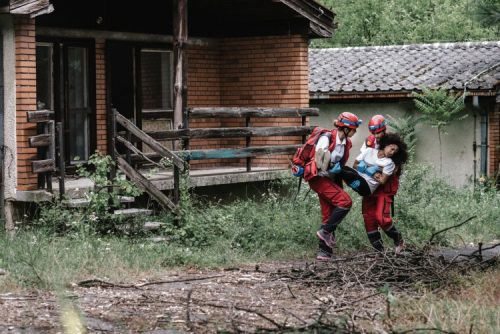 Disaster relief workers aiding a survivor.