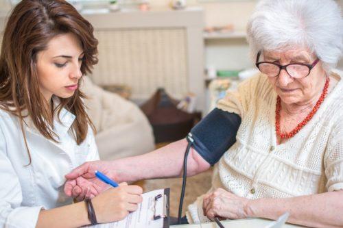 An AGNP tests a patient's blood pressure.