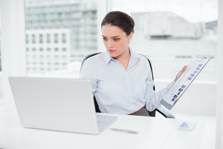 A budget analyst reviews her company's financial report.