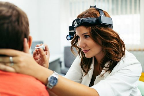 Audiologist performs medical ear examination.