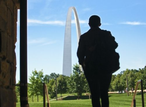 silhouette of person walking toward st louis arch