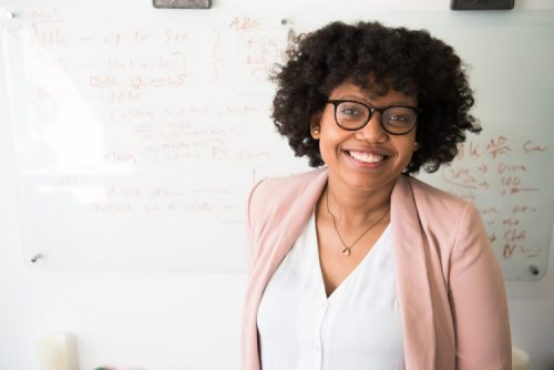 African American woman standing in front of a whiteboard.