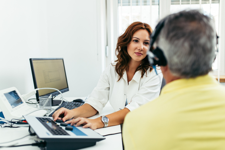 An audiologist assistant conducts a medical hearing examination.