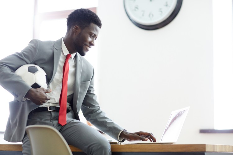 A sports executive holding a soccer ball works on a laptop.