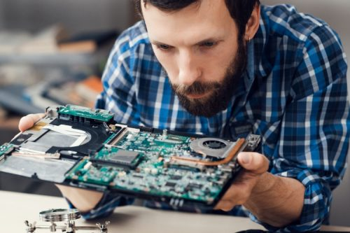 A computer engineer working on a motherboard.