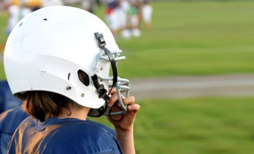 A profile shot of a young football player with a blue uniform and a white helmet. Other children can be seen on the grassy field in the background.