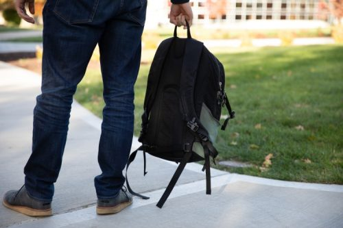 student holding backpack by legs