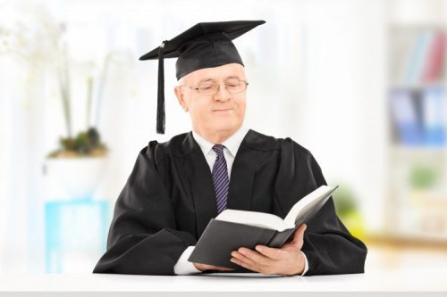 A college dean looks at a book prior to a graduation ceremony.