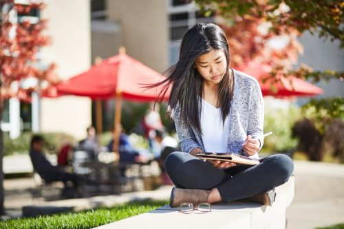 student sitting outdoors with tablet looking down