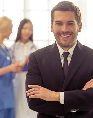 man in suit standing in front of three healthcare professionals