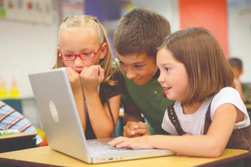 Three children surfing the web on a computer in a classroom monitored by a teacher