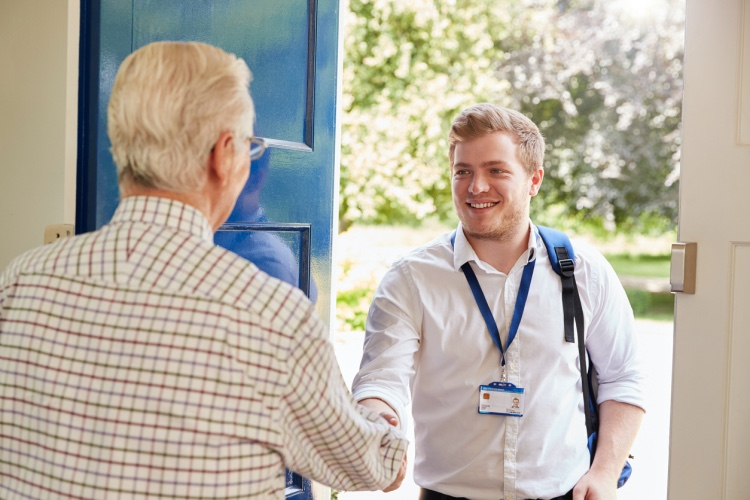 A social worker visits an elderly man at home