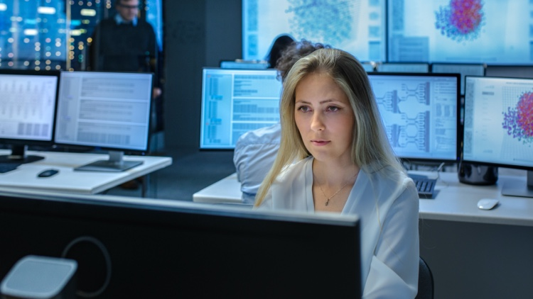 A female cybersecurity specialist works in a data center