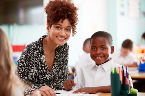 A smiling teacher works with an elementary student