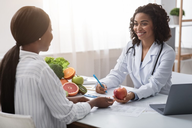 A nutritionist in a white coat holds an apple during a consultation with a client