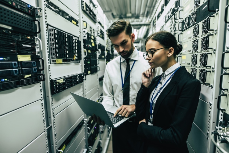 a man and a women looking at a laptop in a server room