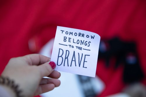 hand holding white sticky note tomorrow belongs to the brave