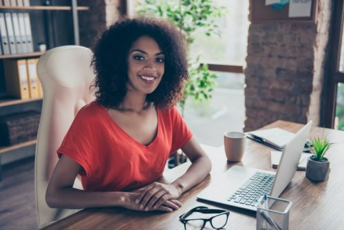 A female compensation and benefits manager sits at her office desk.