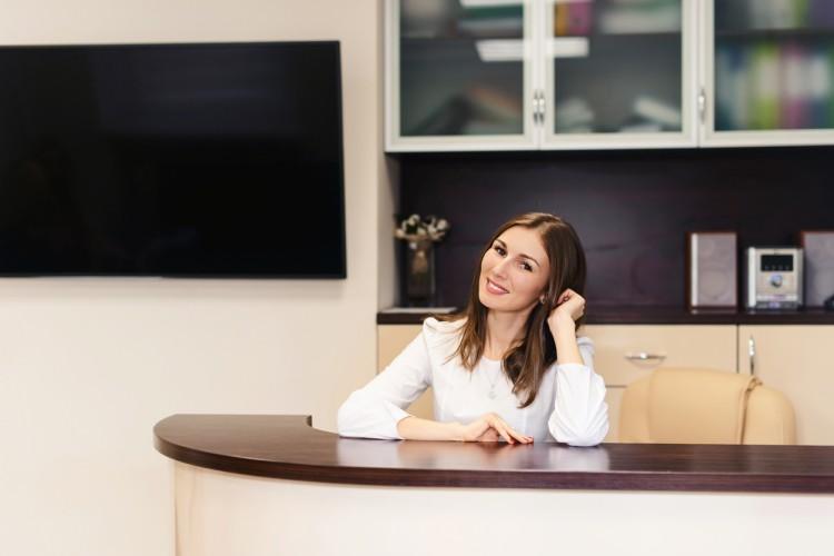 A smiling woman sits at a reception desk at a hospital
