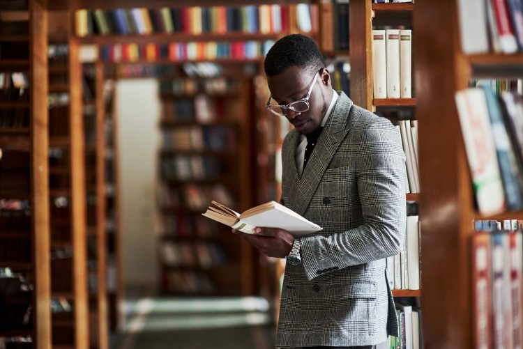 A forensic psychologist in professional attire stands next to some library shelves looking at an open book in his hands