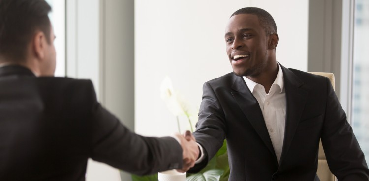 A smiling HR manager shakes a new hire's hand.