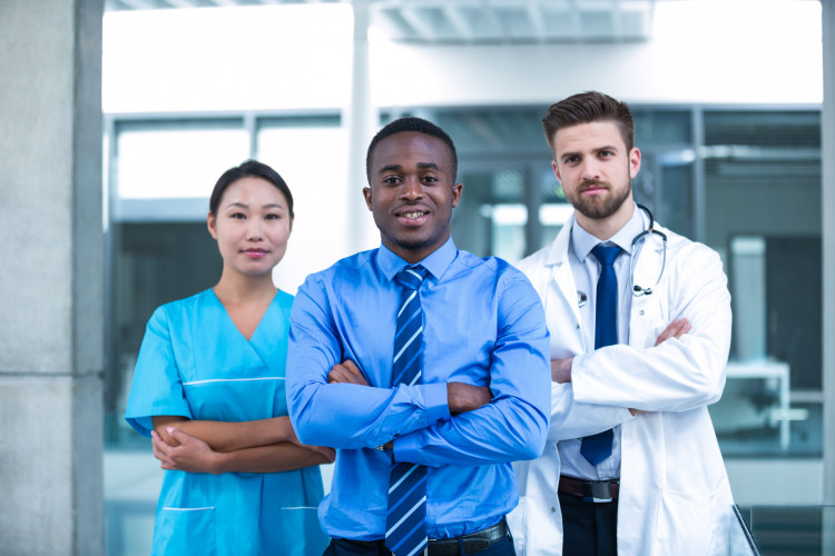 A health manager stands with a doctor and a nurse in a hospital