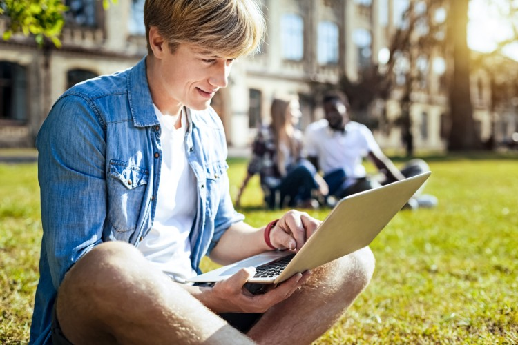 A student sits on a sunny lawn in front of a college building studying on a laptop.