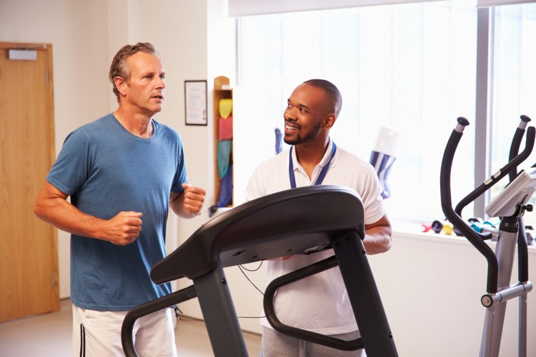 An exercise physiologist watches a man running on a treadmill in a hospital physical therapy department
