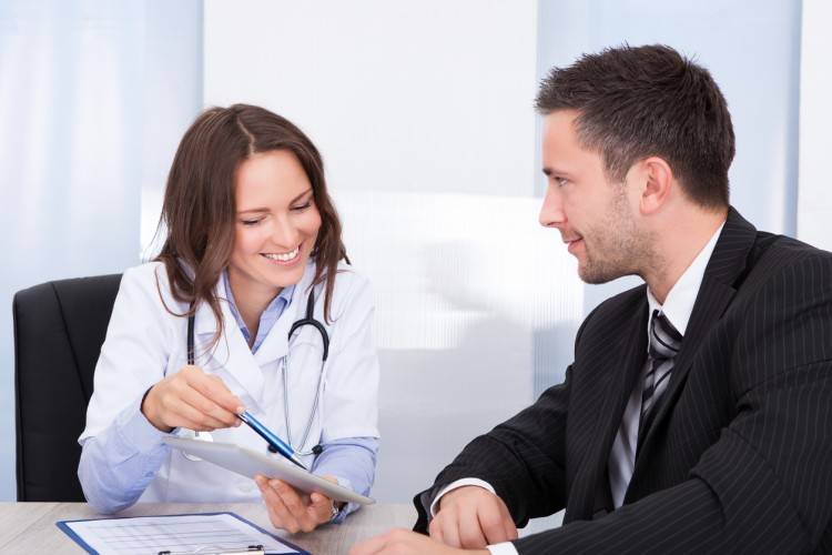 A doctor, pointing to a document, and a social worker sit at a conference table.
