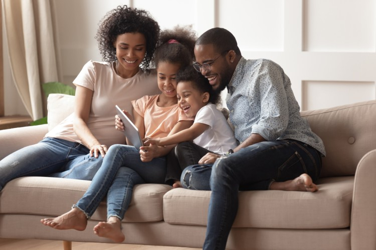 A family of two parents and two young children sit crowded together on a living room couch smiling and looking at a tablet held by one of the children