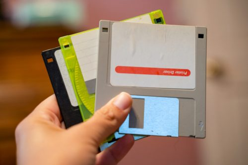 A hand holds three floppy disks