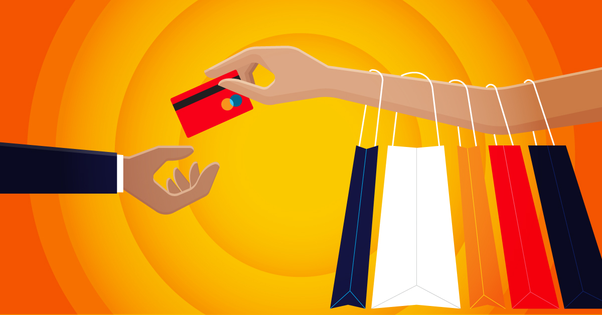 A person's arm holding shopping bags and a credit card.