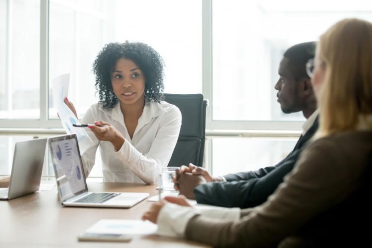 Business development manager meets with potential clients in her office