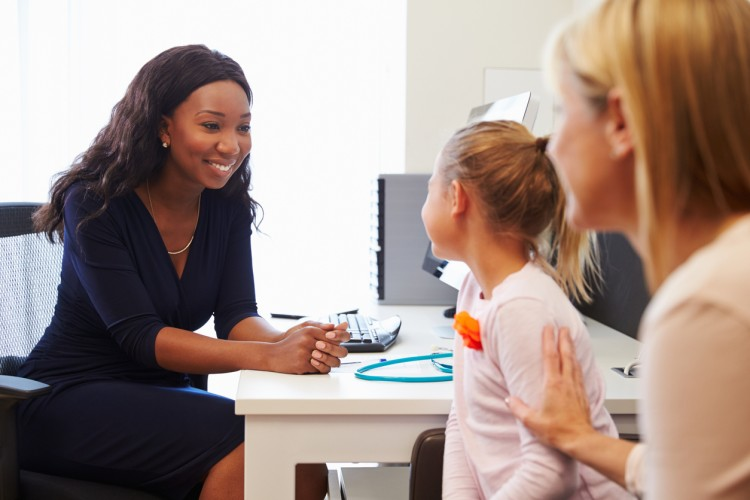 A child life specialist meets with a young patient and her mother.