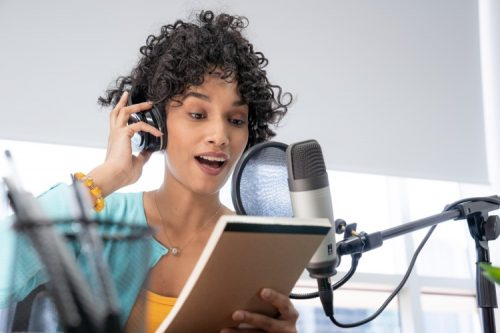 A podcaster reads from a script into a microphone.