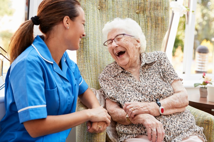 A young gerontology nurse in blue scrubs is seated beside a laughing elderly person