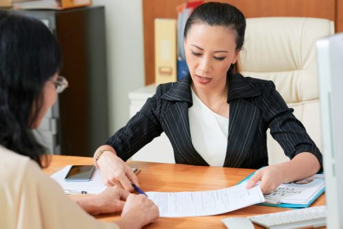 A social worker sitting at a desk showing paperwork to a client.