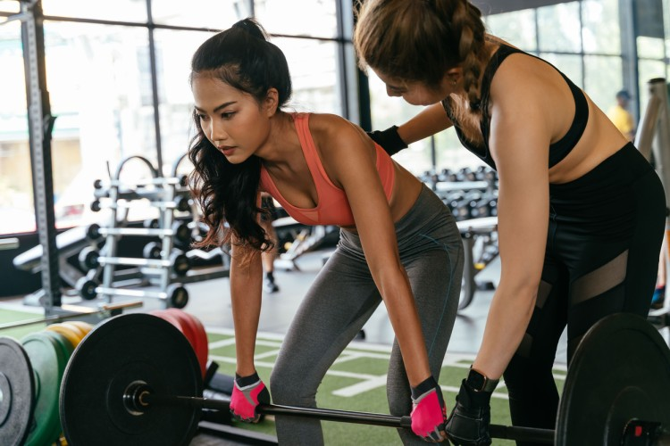 A personal trainer helps a client with weight training