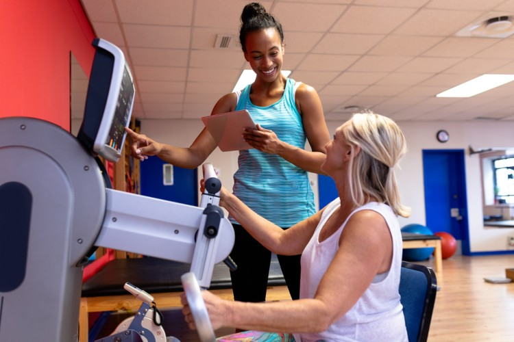 An athletic trainer works with a client on an exercise machine