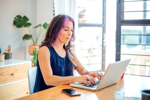 woman typing on laptop with phone on table