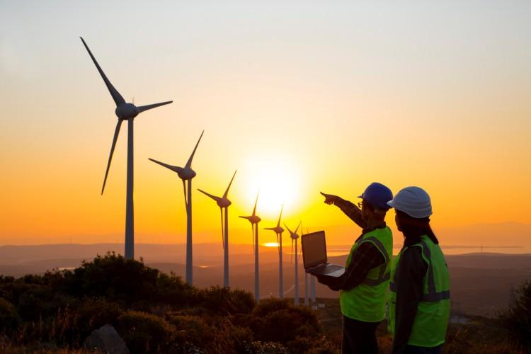 Two wind turbine technicians survey a wind farm as the sun sets.